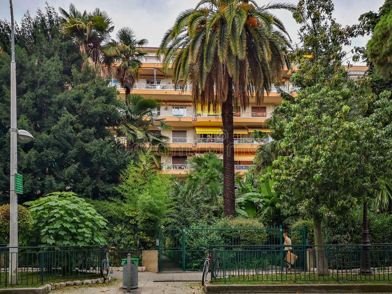 Woman opens a fence door and enters a closed green yard of a nice house in Nice, France stock image