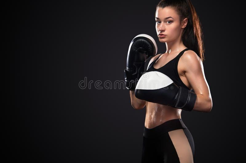 Woman boxer in boxing gloves on black background. Boxing and fitness concept. Street fighter fighting in boxing gloves. Isolated on black background with copy stock image