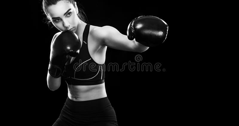 Download woman boxer fighting in boxing cage isolated on black background copy space