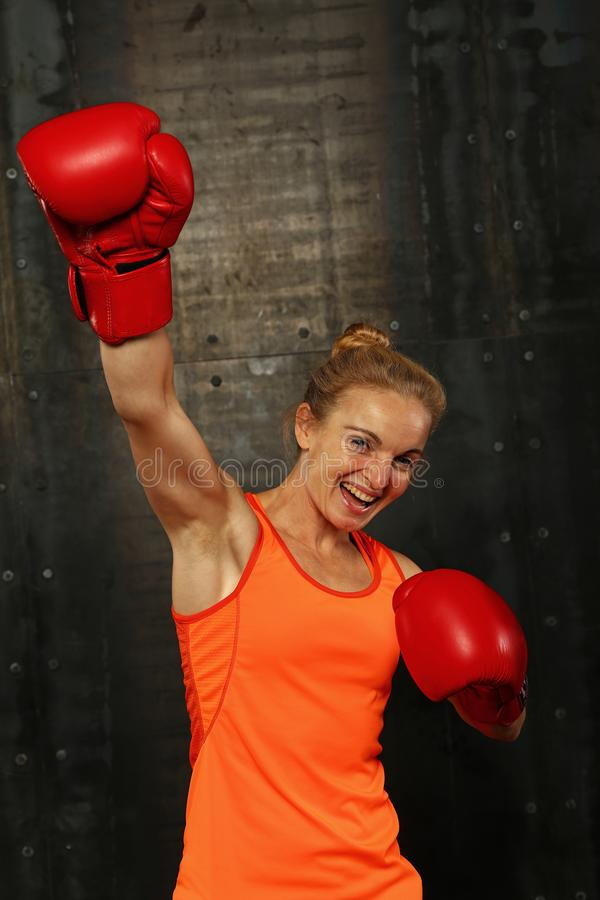 Woman in boxing gloves with hand up win gesture royalty free stock image