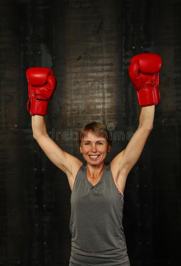 Woman in boxing gloves with hand up win gesture stock images