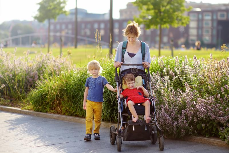 Woman with a boy and a disabled girl in a wheelchair walking in the park at summer. Child cerebral palsy. Family with disabled kid. Woman with a boy and a royalty free stock image