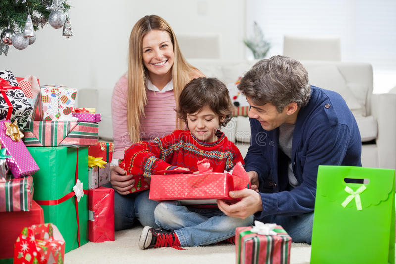 Woman With Boy And Man Opening Christmas Gift. Portrait of happy women with boy and men opening Christmas gift at home royalty free stock image