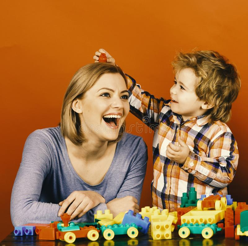 Woman and boy play on red background. Childhood and playing. Concept. Mom and kid in playroom. Family with happy excited faces build toy cars out of colored stock photos