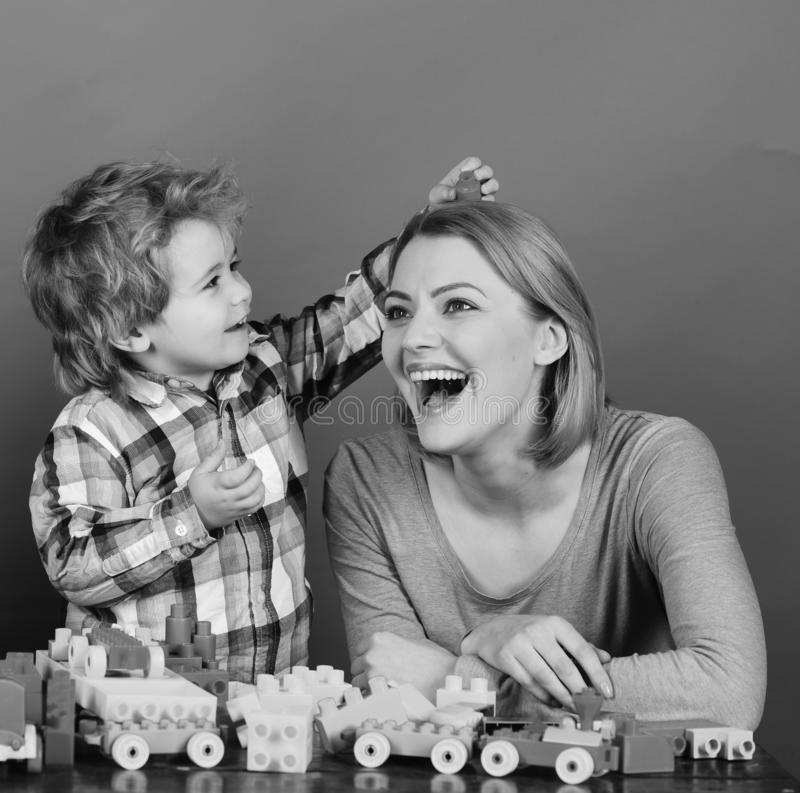 Woman and boy play on red background. Childhood and playing. Concept. Mom and kid in playroom. Family with happy excited faces build toy cars out of colored royalty free stock photo