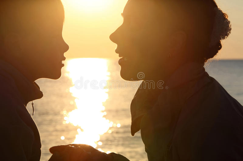 Download Woman With Boy Sit Ashore Opposite Sun Stock Image - Image: 17215777