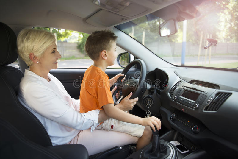 A woman and a boy sitting in a car learning to drive royalty free stock images