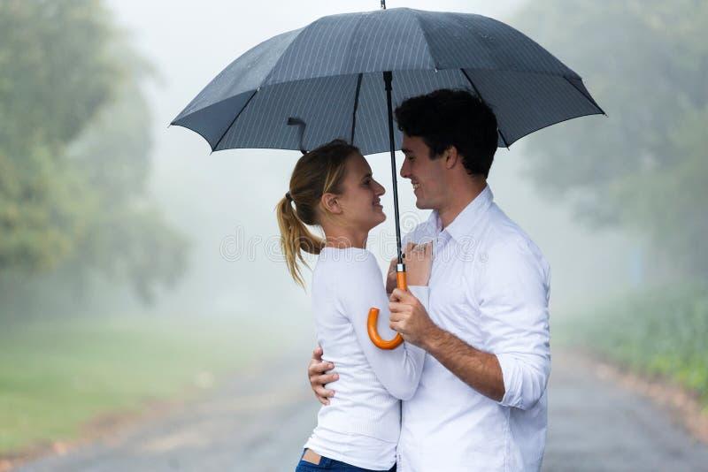Woman boyfriend umbrella. Lovely young women with boyfriend under an umbrella in the rain stock photos