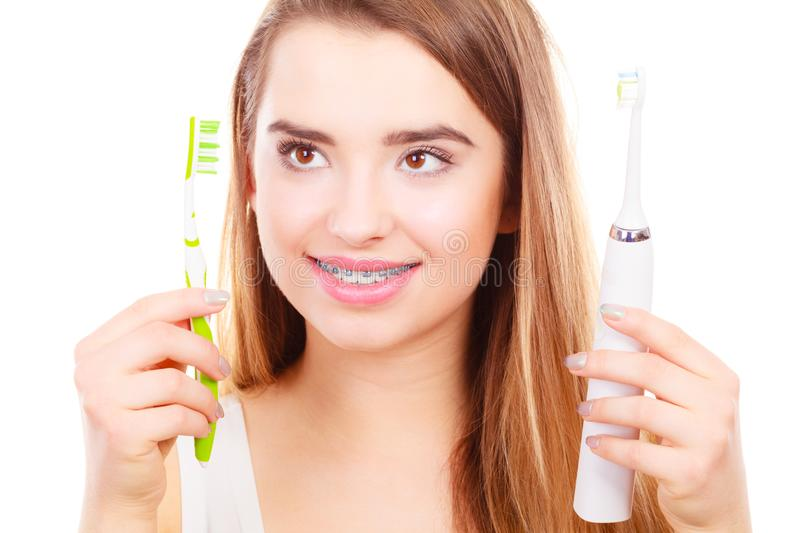 Woman with braces holding electric and traditional toothbrush royalty free stock photo