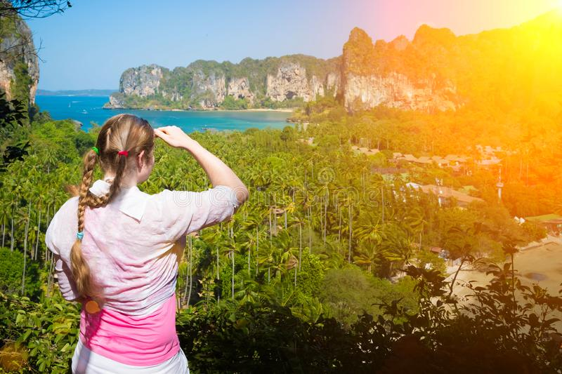 Woman with braids in pink shirt is standing on the peak of mountain and watching over the jungles and two sandy tropical beaches. Railay in Krabi province stock image