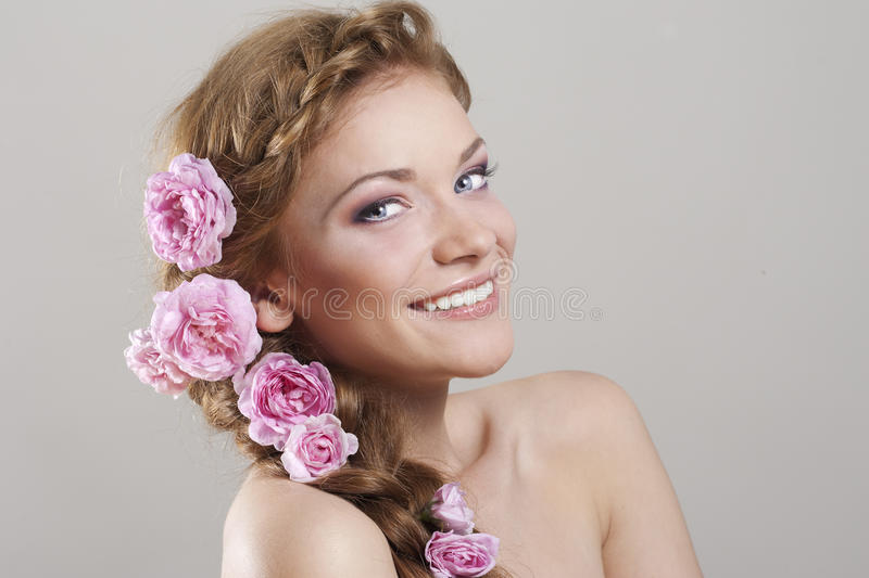 Woman with with braids and roses in hair. Portrait of young woman with with braids and flowers in hair royalty free stock photography