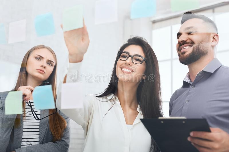 Woman brainstorming using adhesive notes on glass wall stock photos