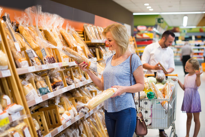 Woman in bread section in food store. Smiling young women picking bread from shelf in food store stock photography