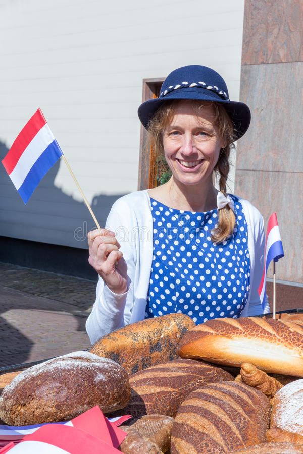 Woman with breads waving with dutch flag. Caucasian middle aged woman with breads waving with dutch flag on vliberation day to celebrate peace and freedom in the stock photos