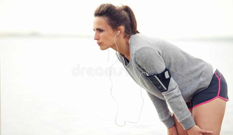 Woman On A Break After Jogging. Focused female runner on a break after running workout royalty free stock image