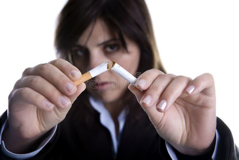 Woman breaking cigar - anti-tobacco concept. Woman breaking cigar isolated on white - anti-tobacco concept stock photos
