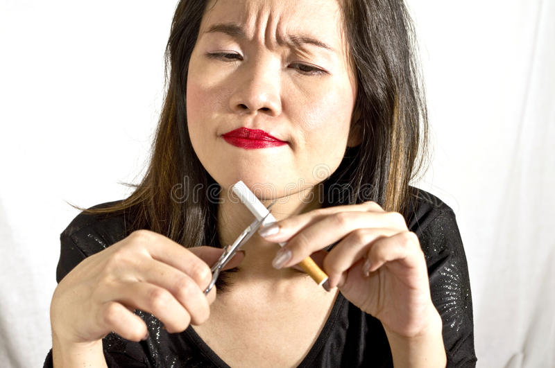 Woman breaking cigarette. Portrait of woman in action stock photo
