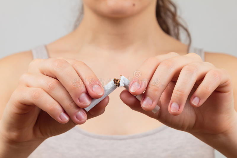 Woman breaking a cigarette. Quit smoking concept stock images