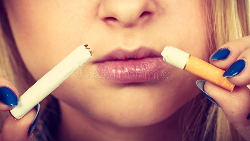 Woman breaking cigarette, getting rid of addiction. New Year resolutions, bad habits, unhealthy lifestyle concept. Woman breaking cigarette, getting rid of royalty free stock photo