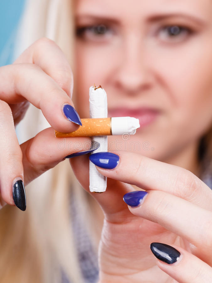 Woman breaking cigarette, getting rid of addiction. New Year resolutions, bad habits, unhealthy lifestyle concept. Woman breaking cigarette, getting rid of stock photo