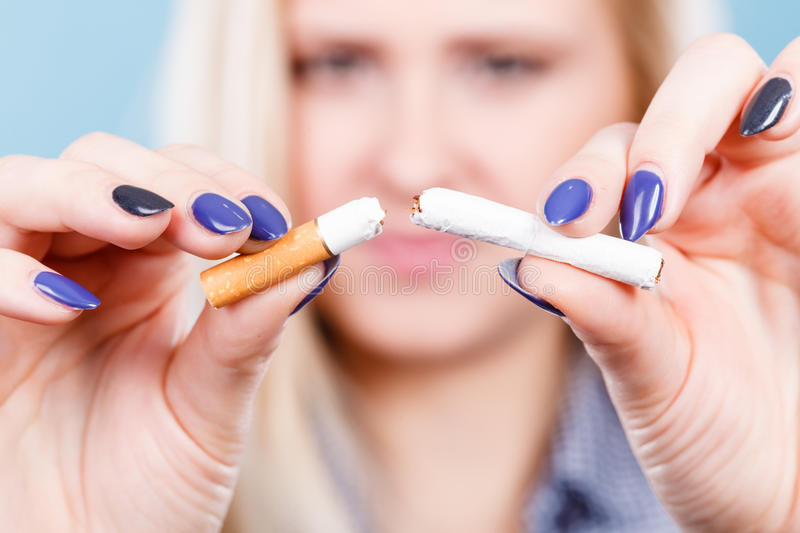 Woman breaking cigarette, getting rid of addiction. New Year resolutions, bad habits, unhealthy lifestyle concept. Woman breaking cigarette, getting rid of stock photography