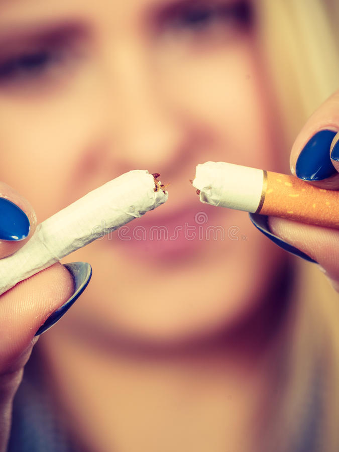 Woman breaking cigarette, getting rid of addiction. New Year resolutions, bad habits, unhealthy lifestyle concept. Woman breaking cigarette, getting rid of royalty free stock image