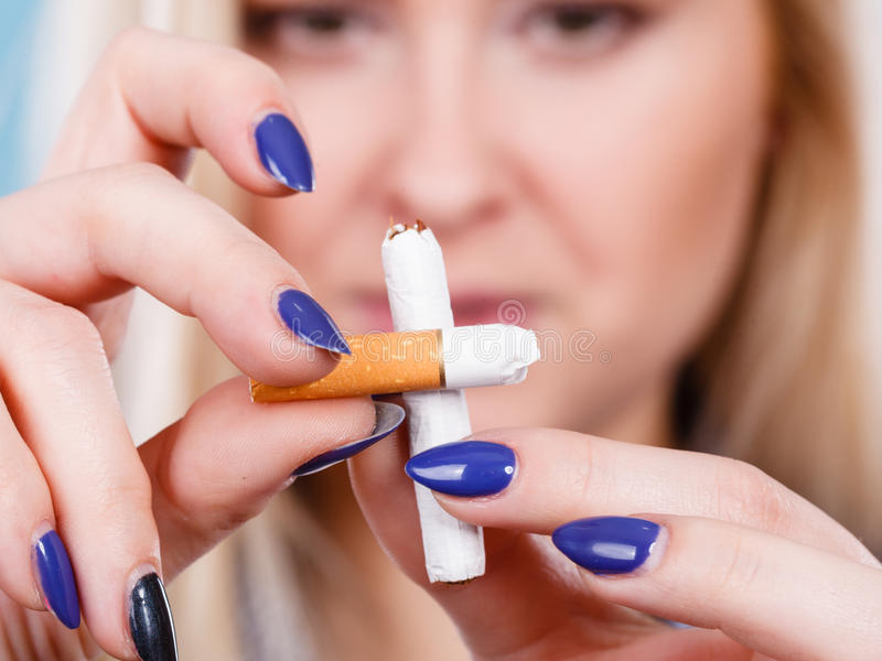 Woman breaking cigarette, getting rid of addiction. New Year resolutions, bad habits, unhealthy lifestyle concept. Woman breaking cigarette, getting rid of stock image