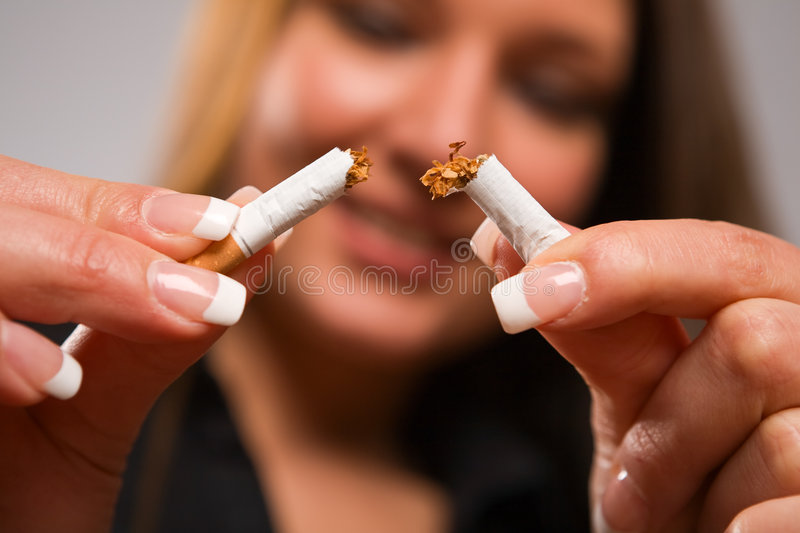 Woman breaking cigarette with manicured hands. Close-up of woman breaking cigarette with her hands - focus on cigarette royalty free stock image
