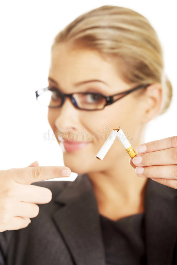 Woman breaking cigarette to stop smoking.  royalty free stock image
