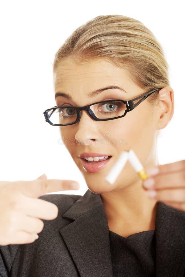 Woman breaking cigarette to stop smoking stock photos