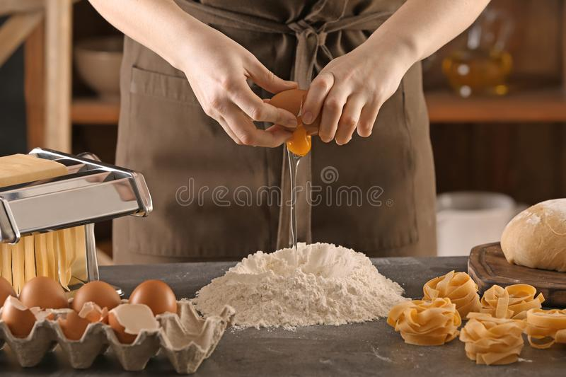 Woman breaking egg into flour at table. Pasta recipe stock photography