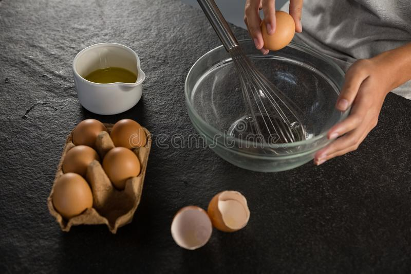 Woman breaking eggs into a bowl. Close-up of woman breaking eggs into a bowl royalty free stock photos