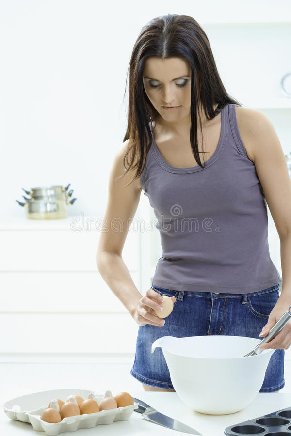 Woman breaking eggs in kitchen. Young woman standing at kitchen table, breaking eggs to a bowl stock image