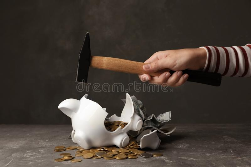 Woman breaking piggy bank with hammer royalty free stock images