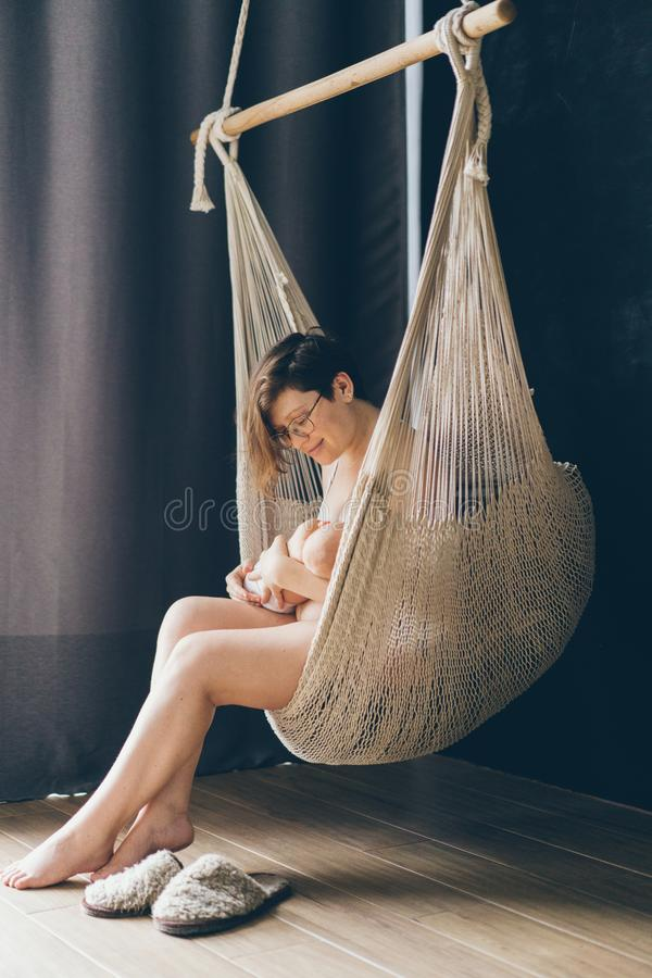 Woman is breastfeeding a newborn baby sitting in a cozy wicker hammock suspended in the interior of the apartment on a dark backgr. Ound near the window stock photo