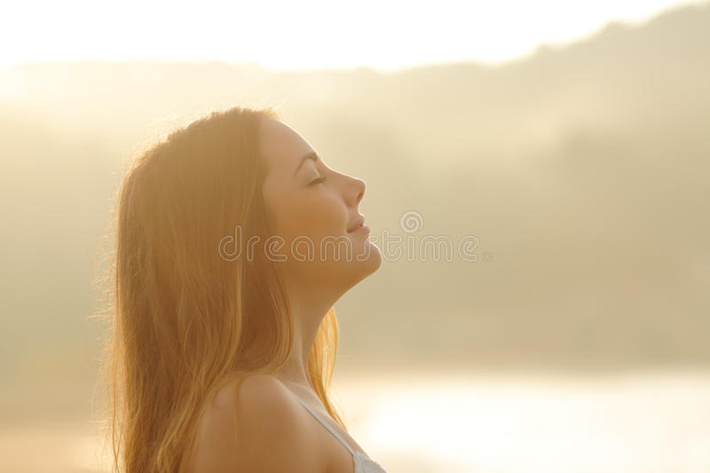 Woman breathing deep fresh air in the morning sunrise royalty free stock photography