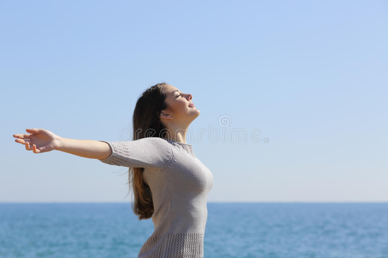 Woman breathing deep fresh air and raising arms. Happy relaxed woman breathing deep fresh air and raising arms on the beach with the horizon in the background stock photo