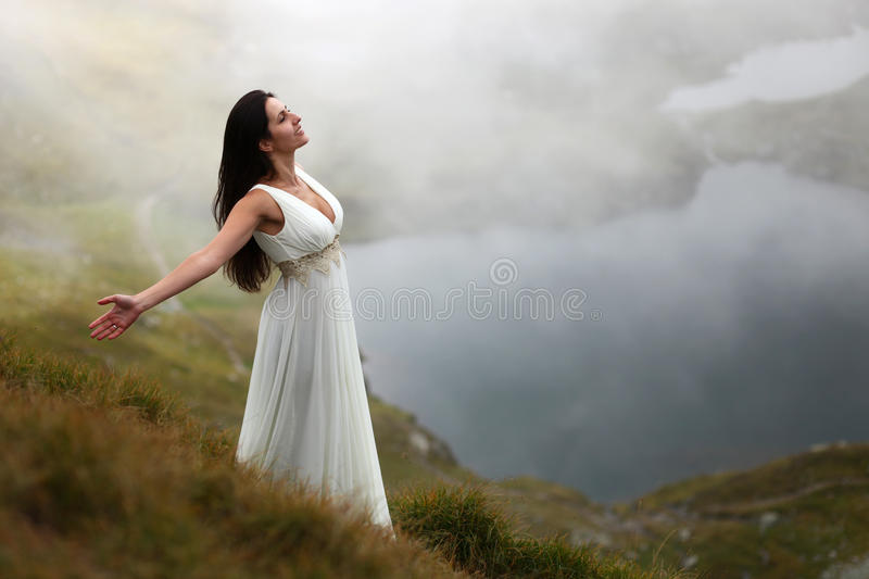 Woman breathing fresh mountain air. Young woman in long white dress breathing fresh mountain air stock photography