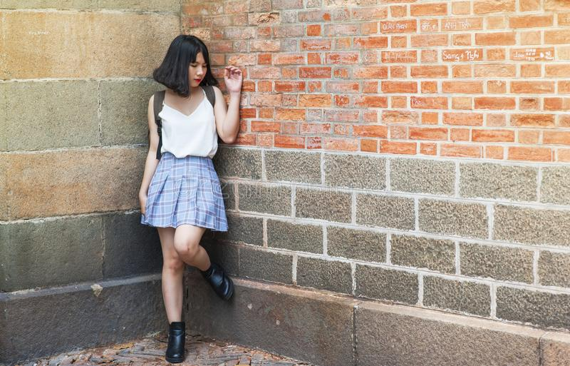 Woman Beside Brick and Cinder Wall royalty free stock photography