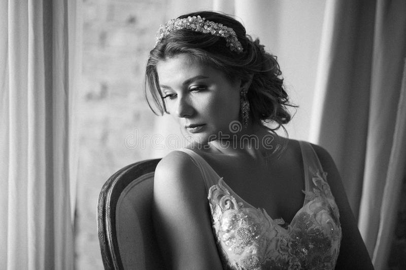 Woman in bridal dress sitting on armchair. Looking down. Indoor, interior, studio royalty free stock photography