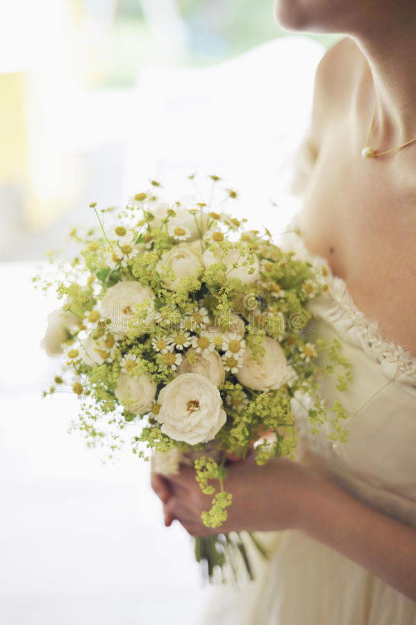 Woman in Bridal Gown Holding Bouquet of White Flowers stock images