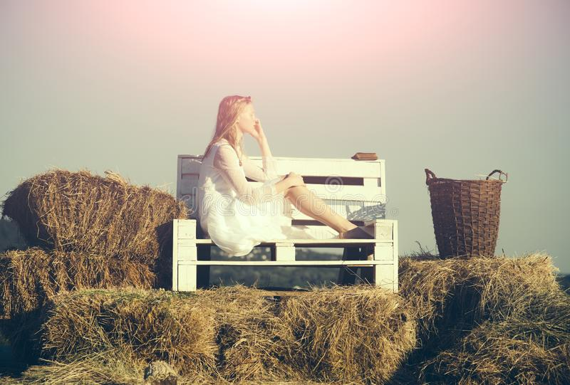 Woman bride in wedding dress relax on wooden bench. Albino girl with wicker basket on hay outdoor picnic. Sexy woman stock images