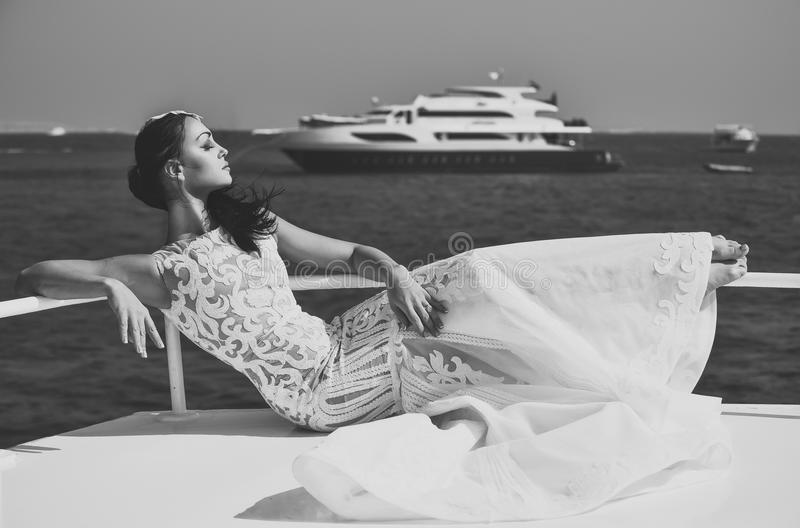 Woman bride in wedding dress relaxing on yacht in sea stock image