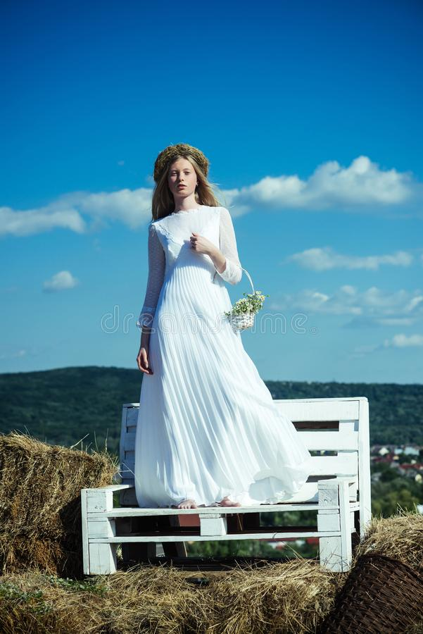 Woman bride in wedding dress on wooden bench. Sensual woman in wreath on long blond hair. Albino girl with flowers stock images