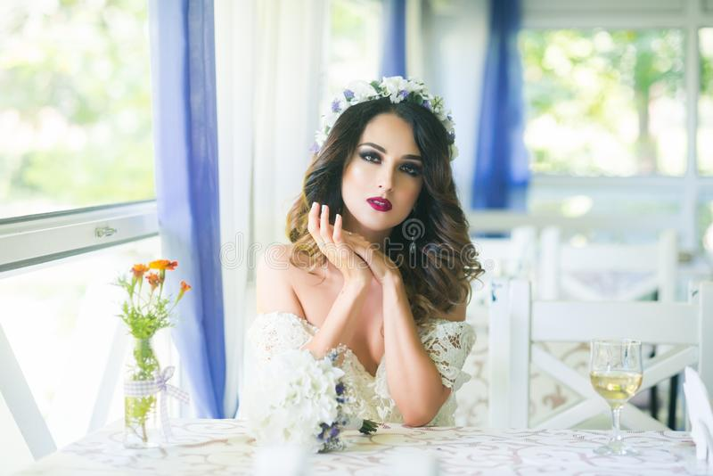 Woman or bride in wreath on long hair in restaurant stock image