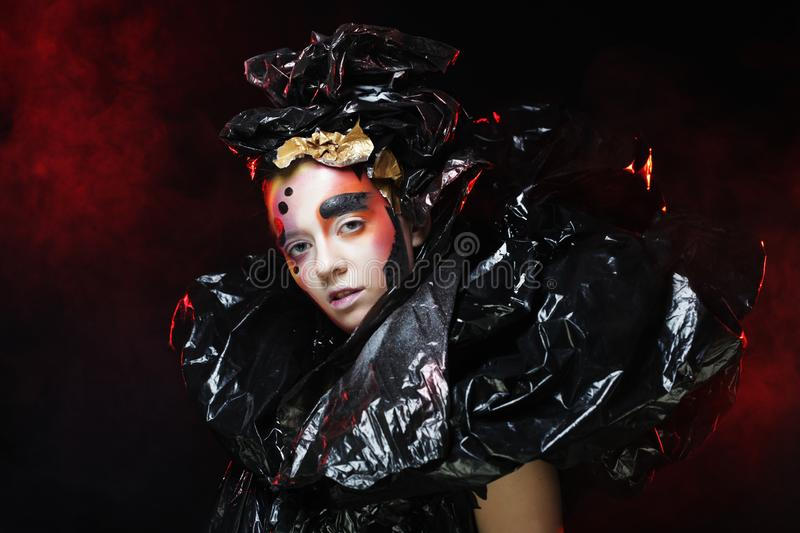 Beautiful young woman with bright fantasy make-up and costume posing on a black background in clouds of smoke. Halloween royalty free stock photography