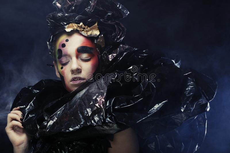 Beautiful young woman with bright fantasy make-up and costume posing on a black background in clouds of smoke. Halloween royalty free stock photo