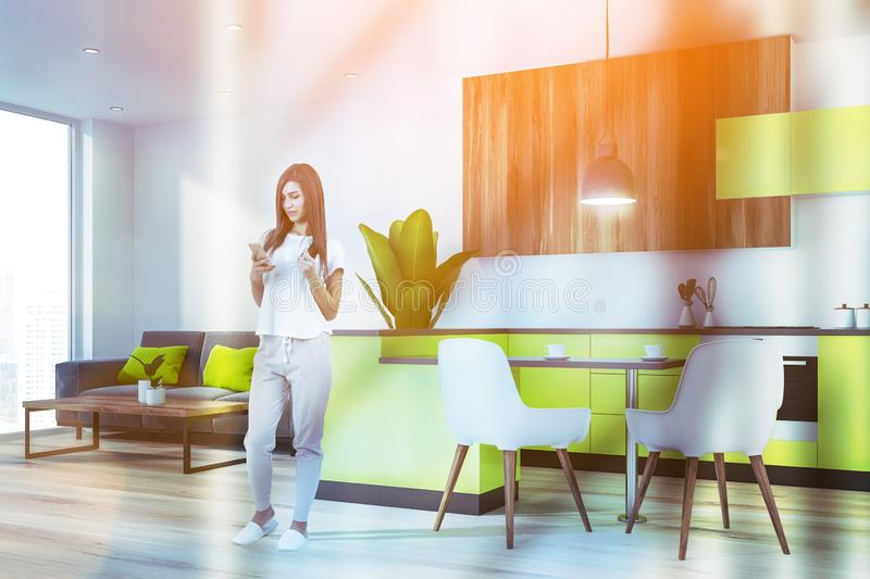 Woman in bright kitchen with sofa stock images