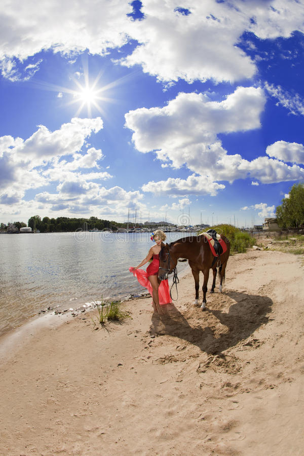 Woman with bright makeup on the horse outdoors. Woman in red dress with bright makeup on the horse outdoors royalty free stock images
