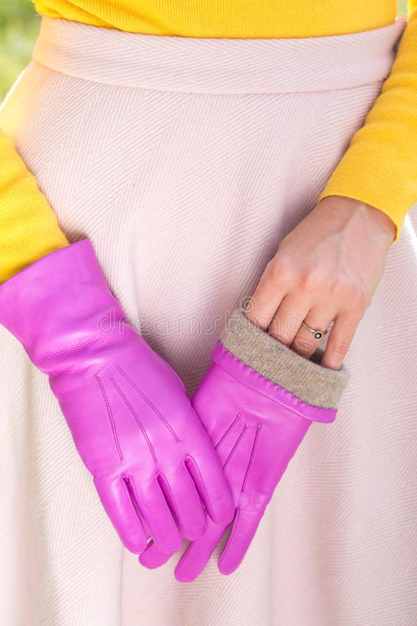 Warm pink gloves. Woman in a bright yellow sweater and pink gloves stock photography